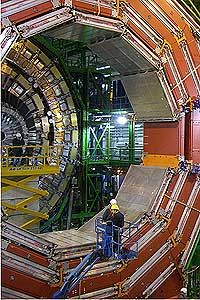 Assembly of the Muon Solenoid structure at CERN. The silver slab is being moved toward the ring with a crane.
