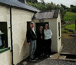 John McGlone and his daughters outside of their ancestors' cottage in Ireland.