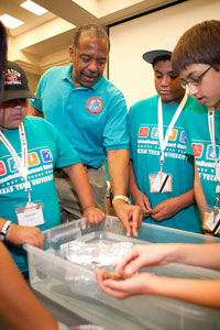 Former astronaut and regent Harris advises campers in the construction and engineering of rafts.