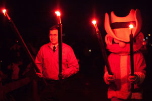 The Saddle Tramps, along with Raider Red, process two by two with flare torches to the math and science quad.