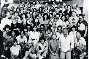 This is a shot of the cast and crew in 1980. Larry Hagman, who played J.R. Ewing on the show, is on the left side of the photo wearing a bow tie. Moore is two people to his right.