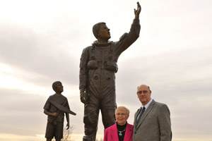 Barry McCool and his wife Audrey pose in front of the Willie McCool memorial statue in South Lubbock.