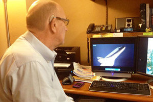 Barry McCool views a documentary about the Columbia Shuttle mission in his office.
