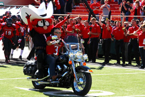 Waller leads the Texas Tech football team onto the field while riding a motorcycle.