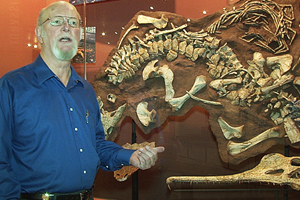 Bill Mueller stands in front of the case that houses the skull, bottom right, of the new phytosaur species.