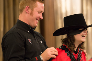 Corey Waggoner places the Masked Rider cape on Mackenzie White.
