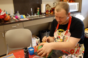 Transition Academy student Brayden Cheshire spends time painting his pumpkin.