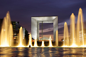 Illuminated fountains dance in front of La Grande Arche de la Defense in Paris, France.