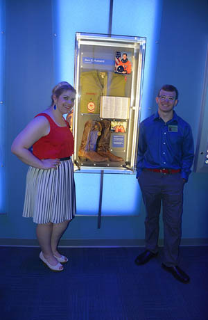 Rick Husband's children Laura and Matthew pose with their father's memorial at NASA's new Forever Remembered: Space Shuttle Memorial exhibit at Kennedy Space Center.