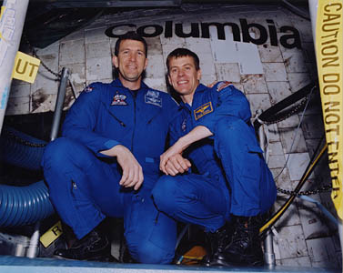 Rick Husband, left, and Willie McCool pose outside the Columbia space shuttle during their training.
