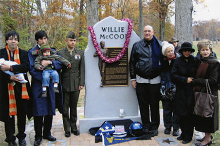 Willie McCool's family pose with his memorial at the Naval Academy.