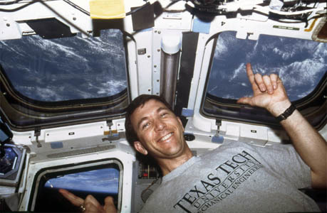 "Rick Husband gives a ""Guns Up"" from space in his Texas Tech University Mechanical Engineering T-shirt."