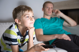 Boy watching tv with dad looking on