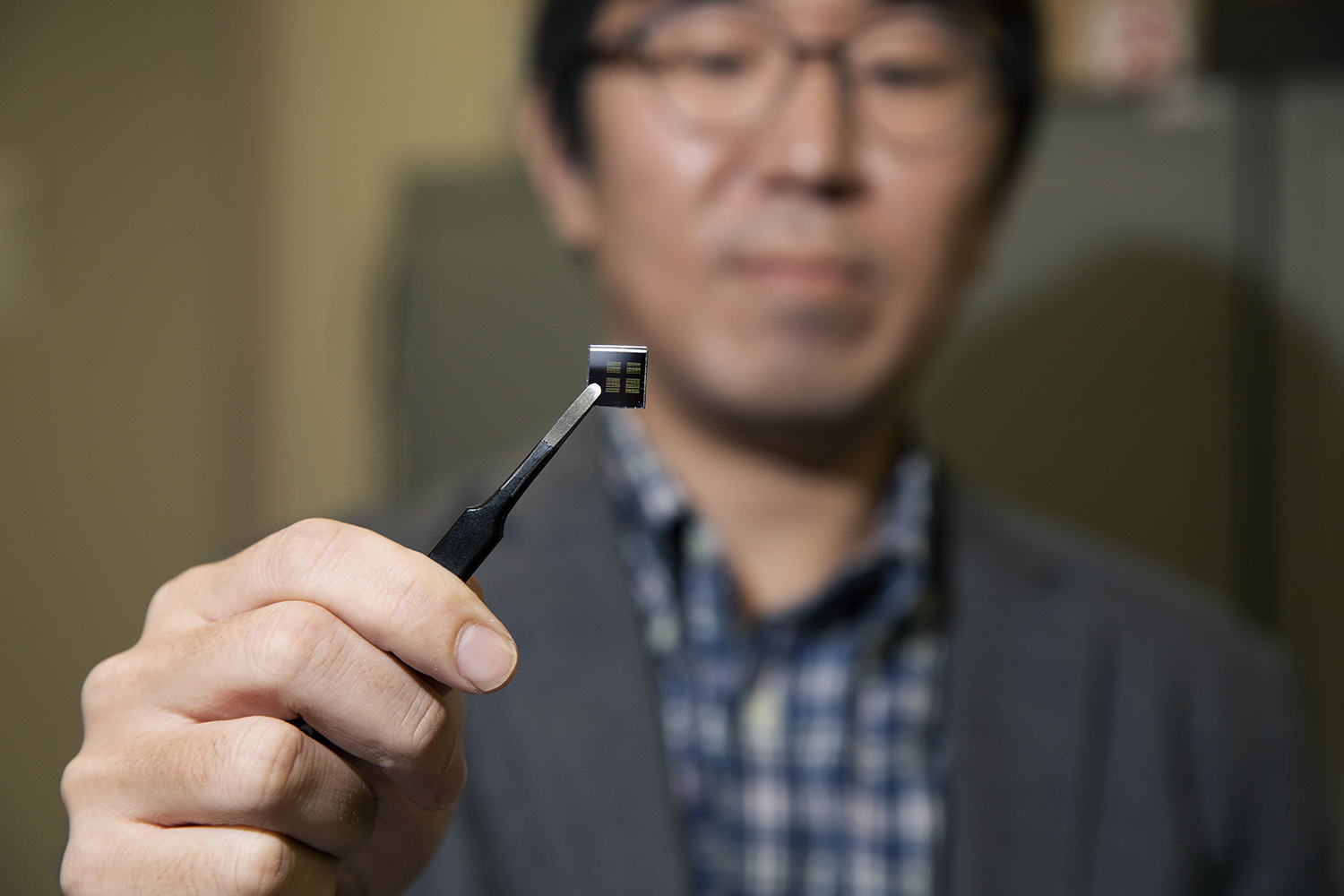 Sangsik Kim holding a photonic chip with tweezers