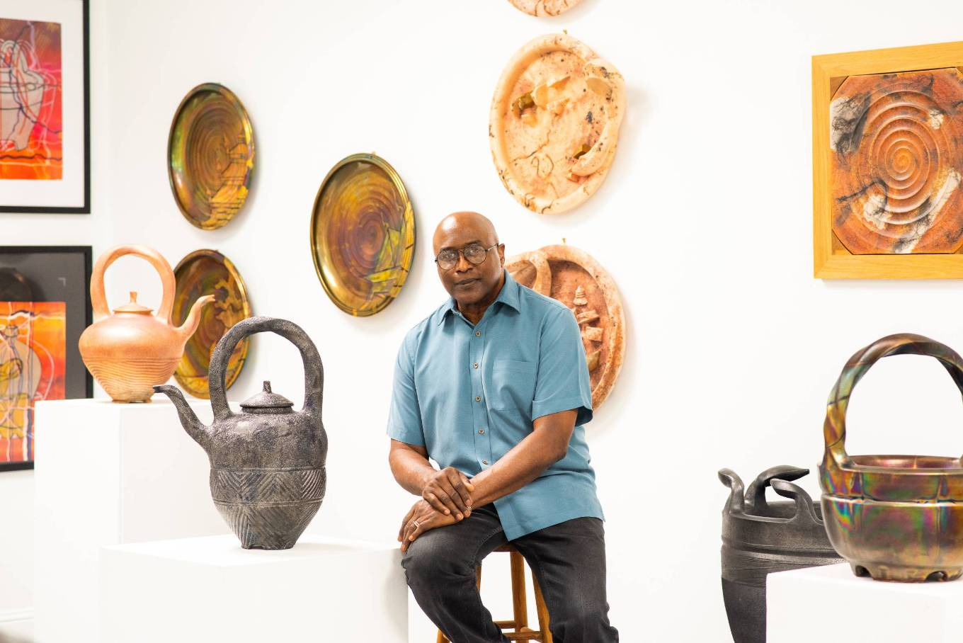 Headshot of Professor James C. Watkins, surrounded by his ceramic work. Photo by Bonni Oakes.